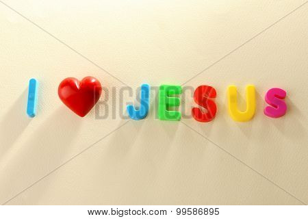 I LOVE JESUS sign illustrated with colorful plastic letters on light textured background