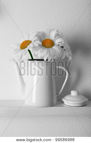 Decorative teapot with flowers on wooden shelf  on white wallpaper background