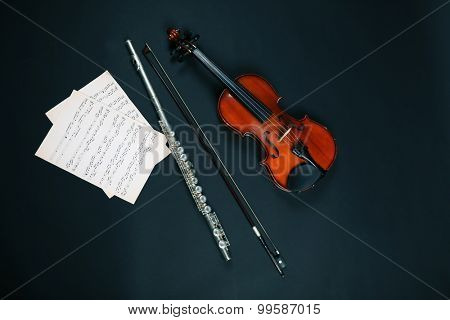 Violin and flute with music notes on dark background