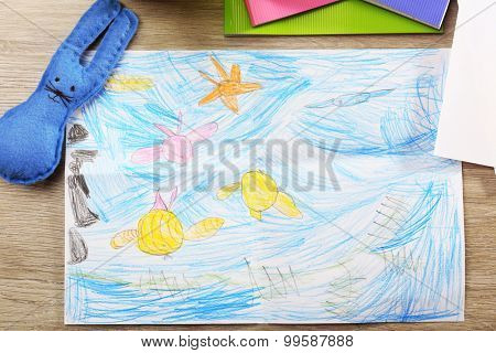 Kids drawing on white sheet of paper on wooden table, closeup