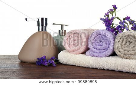 Soft towels with dispenser and flowers on light background