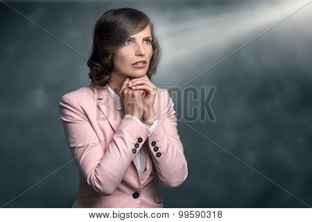 Serious Young Woman With Hands Clasped In Prayer