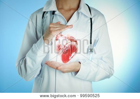 Doctor with stethoscope holding heart, on color background