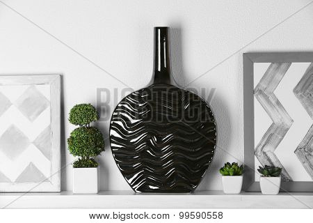 Modern vase with picture on shelf in room