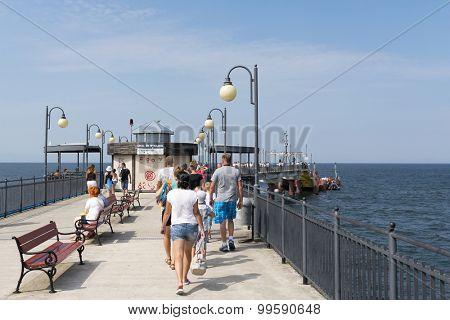 MIEDZYZDROJE - AUGUST 16: Tourists enjoy the sunny weather and walk along the pier on 16 August 2015 in Miedzyzdroje, Poland.
