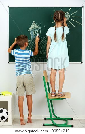 Children drawing on blackboard at school