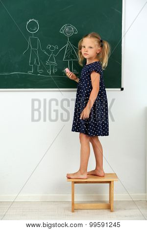 Girl drawing on blackboard at school
