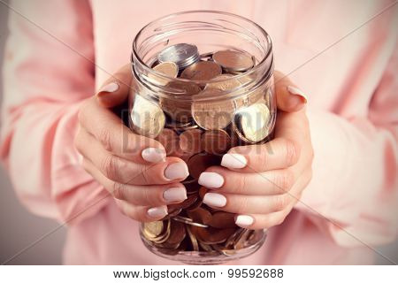 Woman holding money jar with coins close up
