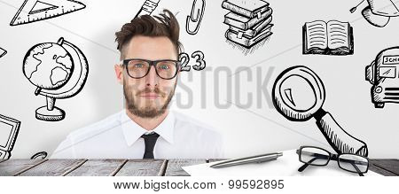 Geeky young businessman looking at camera against desk