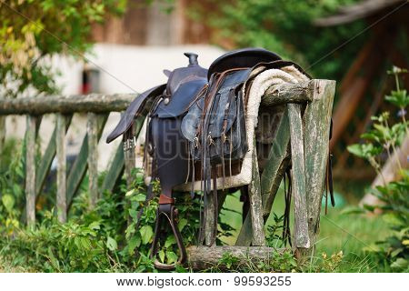 Old Ornamental Saddle On The Wooden Fence