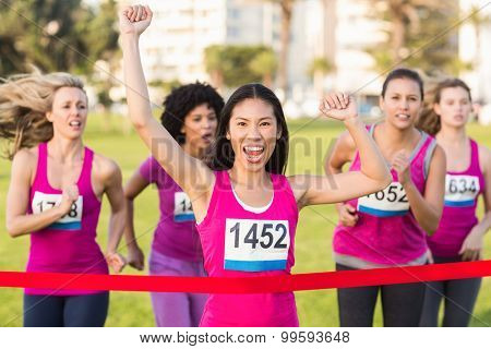 Portrait of cheering woman winning breast cancer marathon in parkland