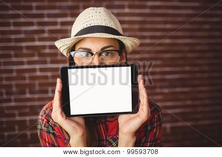Beautiful hipster showing tablet to camera on red brick background