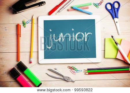 The word junior and students desk with tablet pc against teal, blue