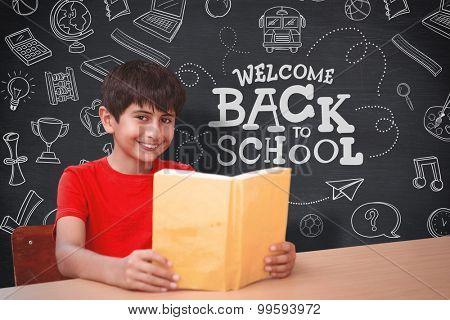 Portrait of boy reading book in library against blackboard