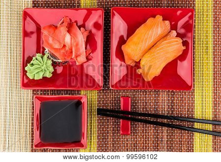 Sushi With Salmon, Soy Sauce, Ginger, Wasabi On Mat