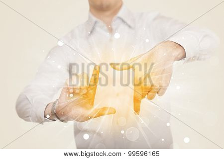 Hands creating a form with yellow shines in the center