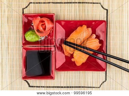 Sushi With Salmon, Soy Sauce, Ginger, Wasabi On Bamboo Mat