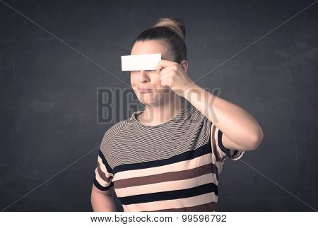 Pretty girl holding blank copy space paper at her eyes concept