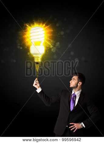 Businessman hold a shining eco-friendly idea bulb on a black background