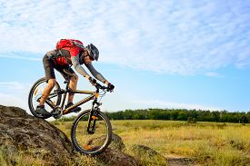 stock photo of exercise bike  - Cyclist Riding the Bike Down Rocky Hill - JPG