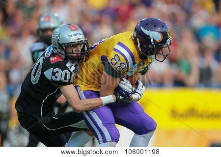 ST. POELTEN, AUSTRIA - JULY 26, 2014: DB Alexander Achammer (#30 Raiders) tackles WR Stefan Postel (#88 Vikings) during Austrian Bowl XXX.