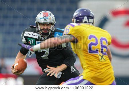 ST. POELTEN, AUSTRIA - JULY 26, 2014: DB Craig Sedunov (#26 Vikings) prepares to tackle QB John Van Den Raadt (#7 Raiders) during Austrian Bowl XXX.