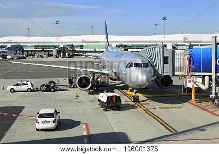 Commercial aircraft being serviced on the tarmac of an international airport.