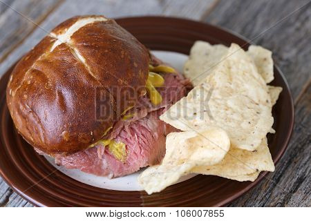 Flank steak sandwich with pretzel bun and mustard