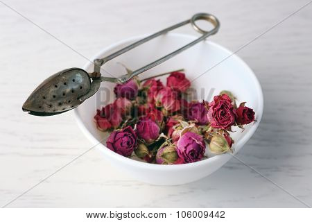 Tea rose in bowl on light wooden background