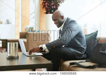Businessman Working On Laptop In Hotel Lobby