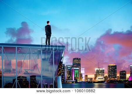 Businessman Standing On The Roof Of A Skyscraper And Looking Over The City At Sunrise