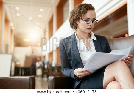 Businesswoman At Lobby Reading Documents