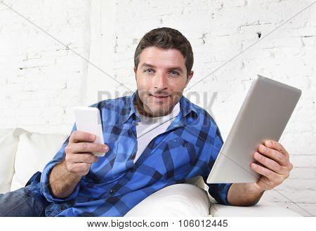 Young Attractive 30S Man Using Mobile Phone And Digital Tablet Pad On Couch Smiling Happy