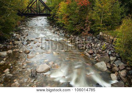 River Flowing Under Railroad Bridge