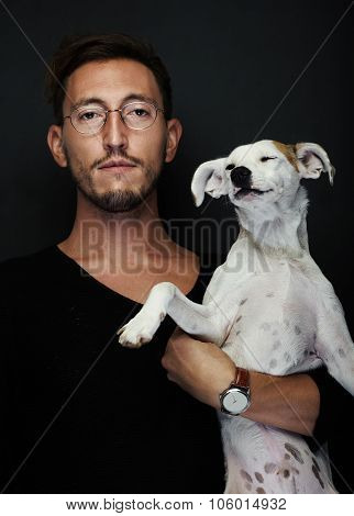 Portrait of handsome young man wearing glasses and holding a dog on his hands. Vertical