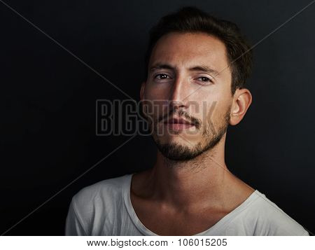 Portrait of cute young man wearing white tshirt and looks serious. Horizontal
