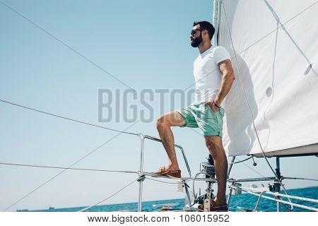Low angle view of young bearded man standing on the nose yacht