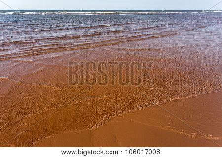 red sand, small waves; Prince Edward Island