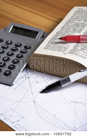 Geometry homework with calculator on wooden desk