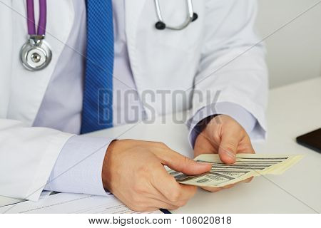 Male Medicine Doctor Holding In Hands Bunch Of Hundred Dollars Banknotes