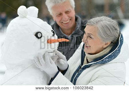 Happy senior couple with snowman