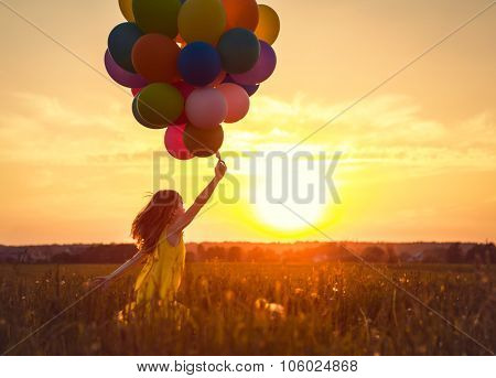 Little girl with balloons on the Sunset
