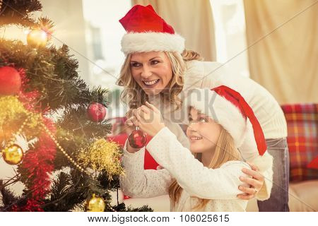 Festive mother and daughter decorating christmas tree at home in the living room
