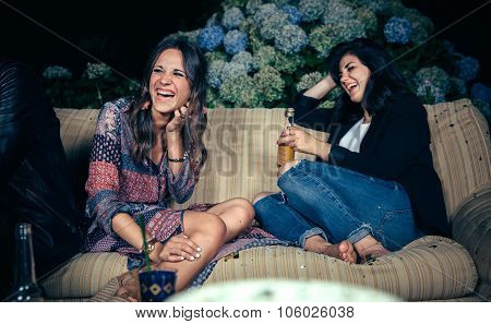 Happy women friends laughing and drinking in a party
