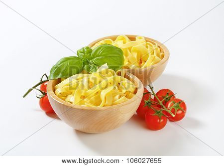 two bowls of fettuccine pasta, basil and cherry tomatoes on white background
