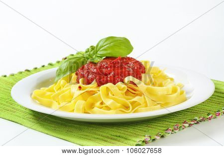 plate of fettuccine pasta and tomato sauce on green place mat