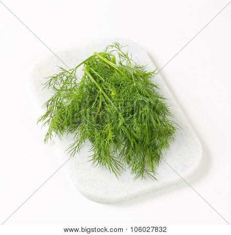 bunch of fresh dill on white plastic cutting board