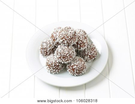 stack of brown coconut truffles on white square plate