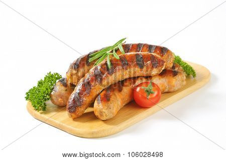 grilled sausages with cherry tomatoes, rosemary and parsley on wooden cutting board