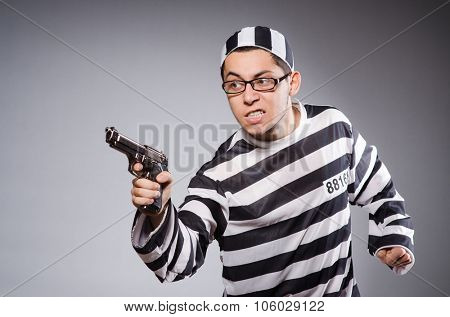 Young prisoner with handgun against gray